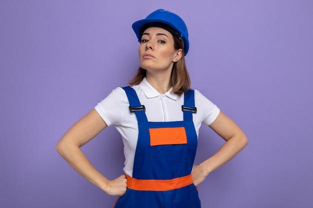 Jonge bouwvrouw in bouwuniform en veiligheidshelm met serieuze zelfverzekerde uitdrukking met armen op heup staande op paars