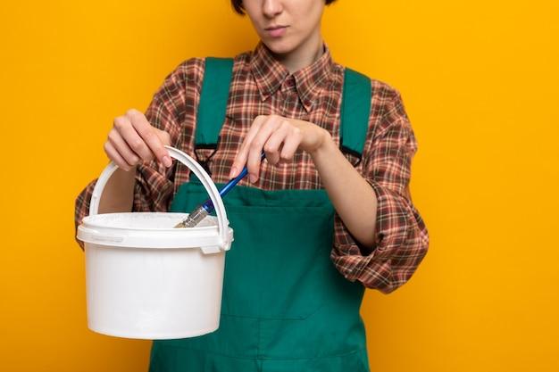 Jonge bouwvrouw in bouwuniform en veiligheidshelm met verfemmer en borstel die over oranje muur staat