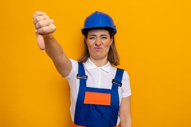 Jonge bouwvrouw in bouwuniform en veiligheidshelm ontevreden met duimen naar beneden staande over oranje muur