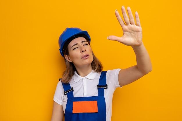 Jonge bouwvrouw in bouwuniform en veiligheidshelm opzij kijkend met loensende ogen die arm op oranje staande houden