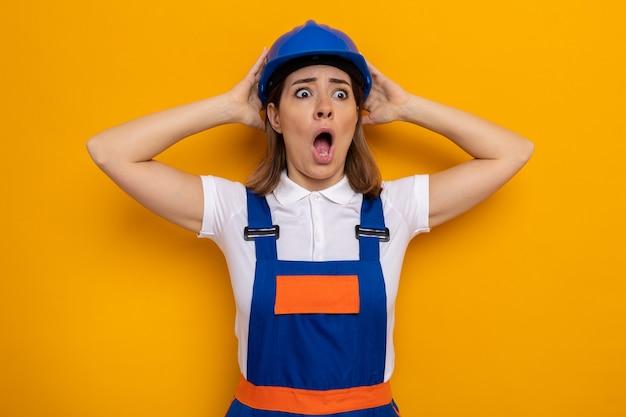 Jonge bouwvrouw in bouwuniform en veiligheidshelm verbaasd en verrast met handen op haar hoofd die over oranje muur staan