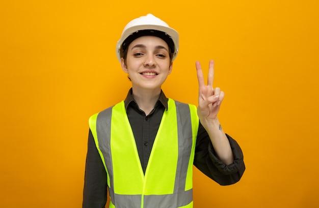 Jonge bouwvrouw in bouwvest en veiligheidshelm, blij en positief glimlachend, vrolijk met een v-teken op oranje