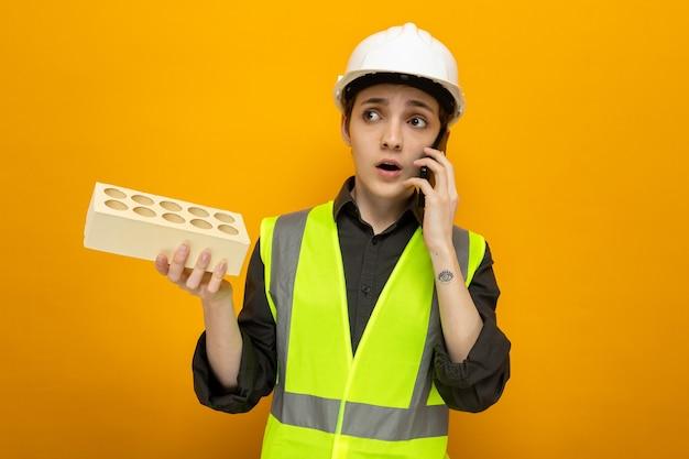 Jonge bouwvrouw in bouwvest en veiligheidshelm die baksteen vasthoudt en er verward uitziet terwijl ze op een mobiele telefoon praat die over een oranje muur staat