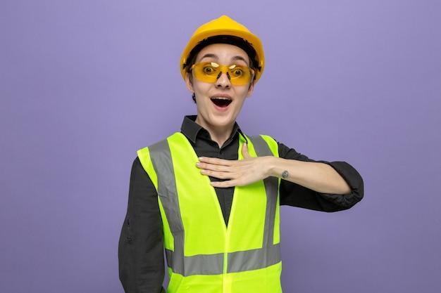 Jonge bouwvrouw in bouwvest en veiligheidshelm die een gele veiligheidsbril draagt, blij en verrast met de hand op haar borst die over de blauwe muur staat