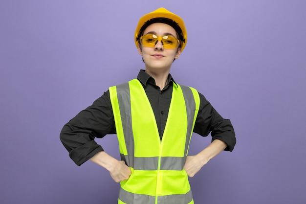 Jonge bouwvrouw in bouwvest en veiligheidshelm die een gele veiligheidsbril draagt met zelfverzekerde uitdrukking met armen op de heup die over blauwe muur staat