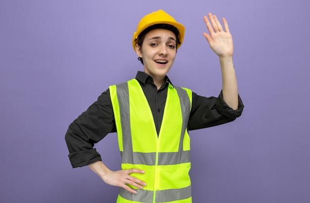 Jonge bouwvrouw in bouwvest en veiligheidshelm die er gelukkig en positief uitziet zwaaiend met de hand