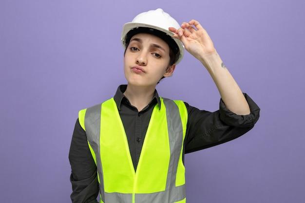 Jonge bouwvrouw in bouwvest en veiligheidshelm die met ernstige zelfverzekerde uitdrukking kijkt en haar helm aanraakt