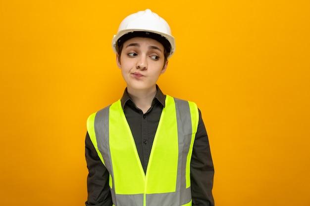 Jonge bouwvrouw in bouwvest en veiligheidshelm die opzij kijkt met een sceptische uitdrukking die over oranje muur staat