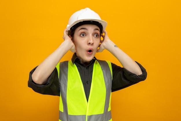 Jonge bouwvrouw in bouwvest en veiligheidshelm die opzij kijkt verbaasd en verrast hand in hand op haar hoofd staande over oranje muur