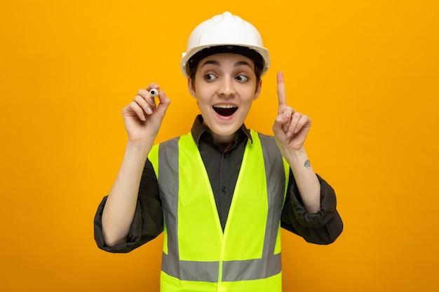 Jonge bouwvrouw in bouwvest en veiligheidshelm die verrast glimlacht en laat zien dat wijsvinger een geweldig idee heeft met pen in de lucht die over oranje muur staat