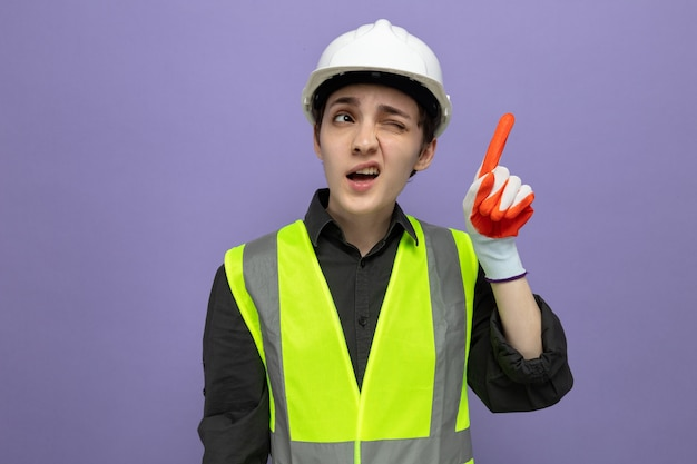 Jonge bouwvrouw in bouwvest en veiligheidshelm in rubberen handschoenen die verward opkijkt en laat zien dat wijsvinger twijfels heeft over paarse muur