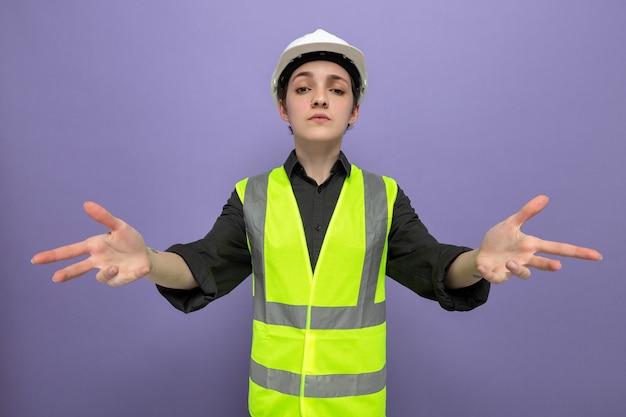Jonge bouwvrouw in bouwvest en veiligheidshelm met ernstige gezichtsverheffing armen in ongenoegen staande op paars