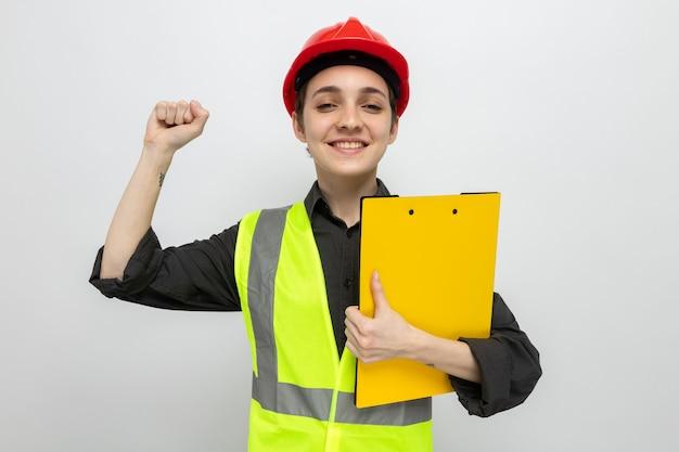 Jonge bouwvrouw in bouwvest en veiligheidshelm met klembord, blij en opgewonden, gebalde vuist over witte muur