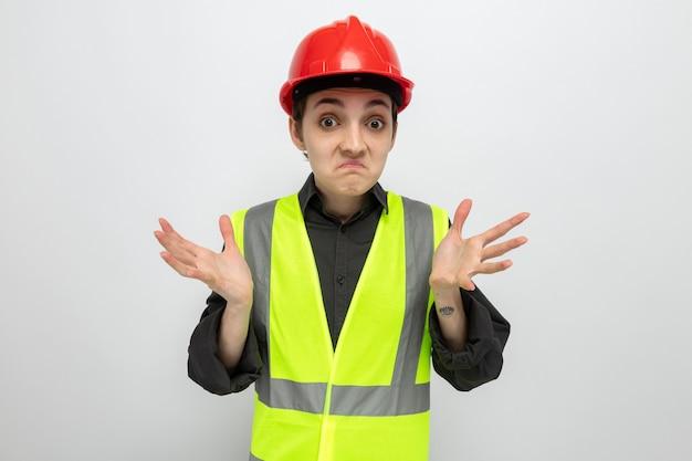 Jonge bouwvrouw in bouwvest en veiligheidshelm verwarde schouders ophalend op wit