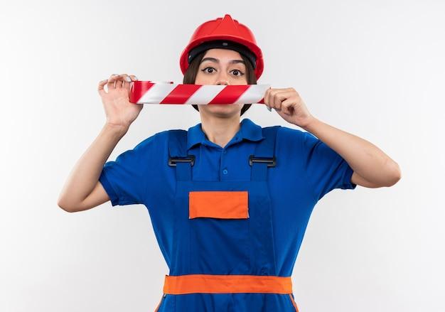Jonge bouwvrouw in uniform bedekte mond met ducttape geïsoleerd op een witte muur