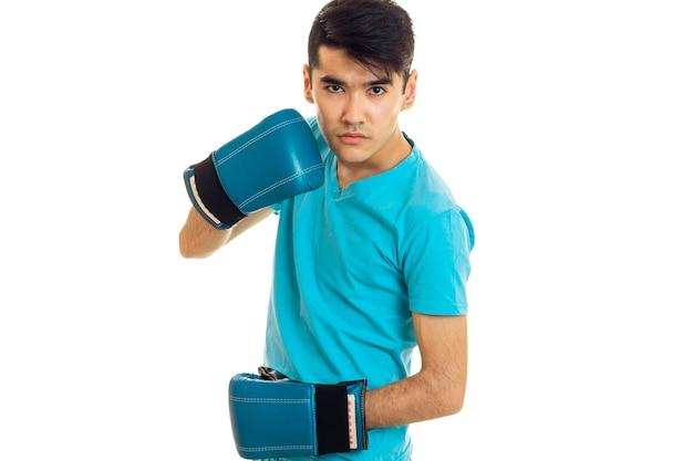 Jonge boze brunette man in blauwe bokshandschoenen oefenen geïsoleerd op een witte muur