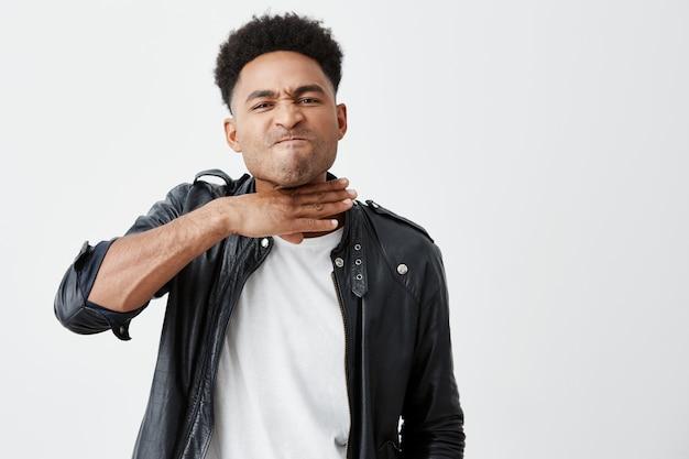 Jonge boze donkere man met afro kapsel in witte t-shit onder zwarte leren jas gebarend met de hand, met uitsnijden hoofdgebaar tijdens ruzie met man op straat
