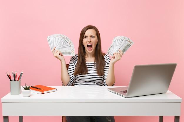 Jonge boze geïrriteerde vrouw schreeuwt handen met bundel veel dollars contant geld werk op kantoor aan een wit bureau met pc-laptop