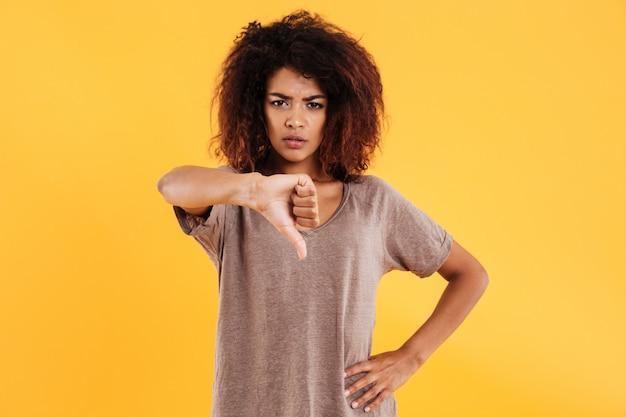 Jonge boze ongelukkige vrouw die neer geïsoleerde duim toont
