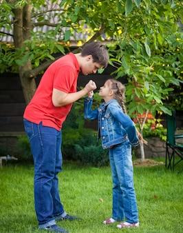 Jonge boze vader en dochter die elkaar aankijken en vuisten vasthouden