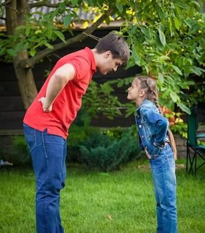 Jonge boze vader en dochter die elkaar aankijken