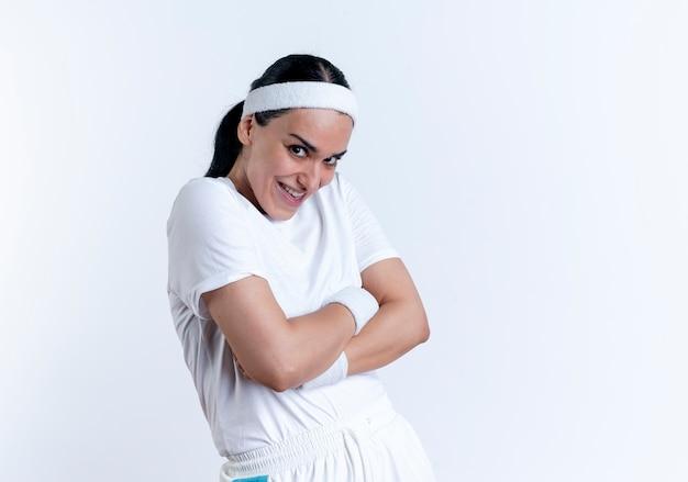 Jonge boze vrolijke blanke sportieve vrouw met hoofdband staat zijwaarts met gekruiste armen