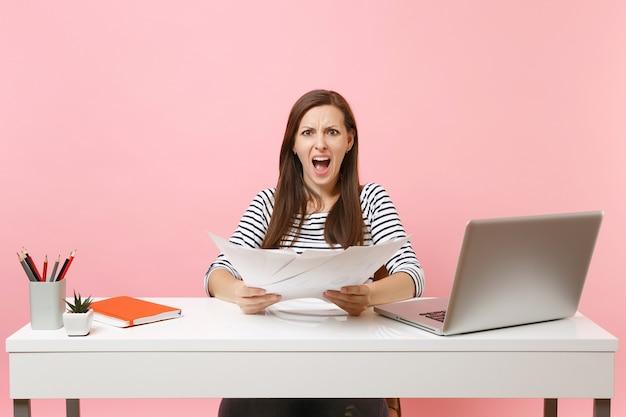 Jonge boze vrouw die problemen heeft met schreeuwen met papieren documenten, aan een project werkt terwijl ze op kantoor zit met een laptop geïsoleerd op een pastelroze achtergrond. prestatie zakelijke carrière concept. ruimte kopiëren.