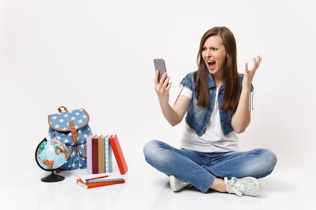 Jonge, boze vrouw die student is, neemt selfie-opname op mobiele telefoon, verspreide handschreeuw, maakt videogesprek in de buurt van geïsoleerde boeken met globe-rugzakken