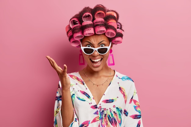 Jonge boze vrouw schreeuwt emotioneel en gebaren met geïrriteerde uitdrukking, draagt haarrollers voor het maken van krullend kapsel, gekleed in casual kamerjas en zonnebril, geïsoleerd op roze muur