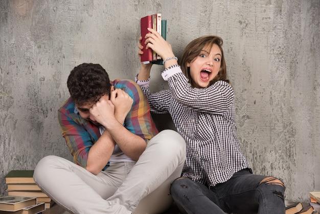 Jonge boze vrouw slaan naar man met boeken