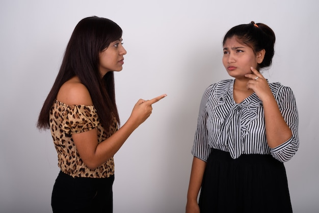 Jonge boze vrouw wijzend op het jonge tienermeisje huilen