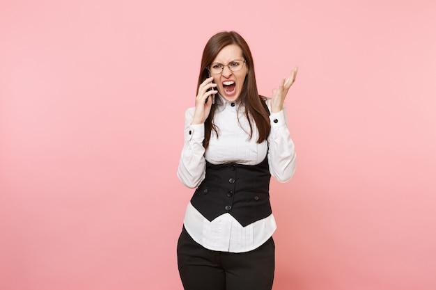 Jonge boze zakenvrouw in zwart pak en bril schreeuwen praten op mobiele telefoon verspreiden handen geïsoleerd op roze achtergrond. dame baas. prestatie carrière rijkdom. kopieer ruimte voor advertentie.