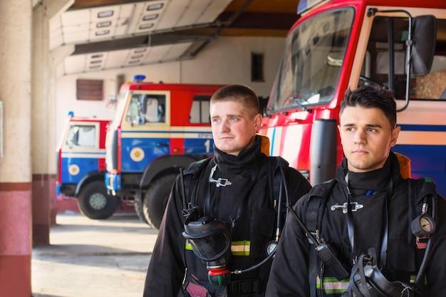 Jonge brandweerlieden op de achtergrond van brandweerwagens