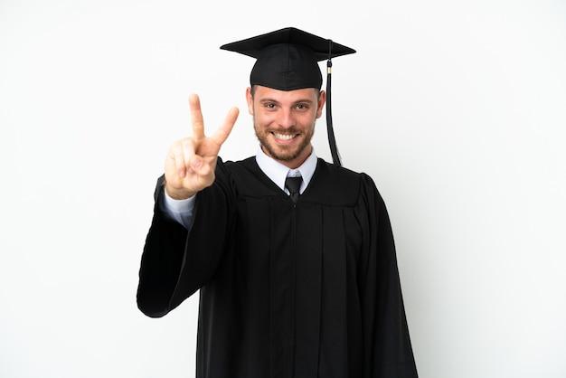 Jonge braziliaanse afgestudeerde universiteit geïsoleerd op een witte achtergrond glimlachend en overwinning teken tonen