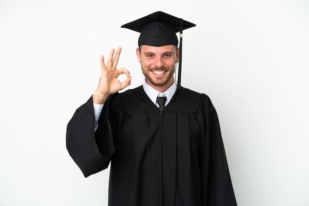 Jonge braziliaanse afgestudeerde universiteit geïsoleerd op een witte achtergrond met ok teken met vingers