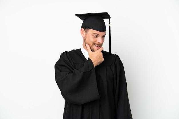 Jonge braziliaanse afgestudeerde universiteit geïsoleerd op een witte achtergrond op zoek naar de kant en glimlachend