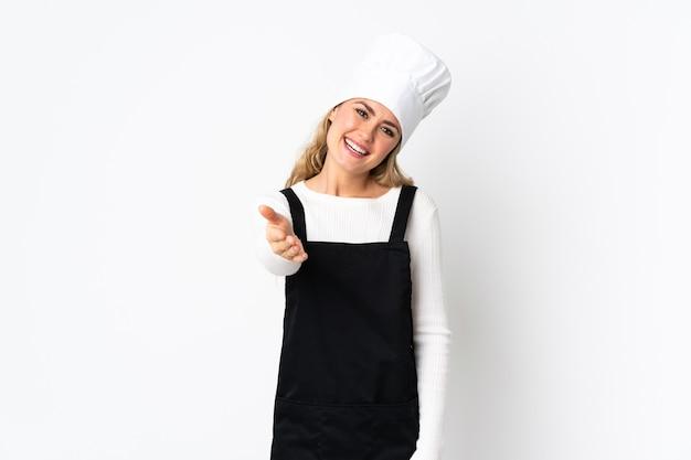 Jonge braziliaanse chef-kok vrouw geïsoleerd op een witte muur handen schudden voor het sluiten van een goede deal