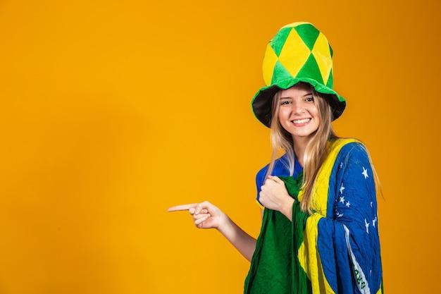 Jonge braziliaanse fan wijst naar de zijkant met ruimte voor tekst