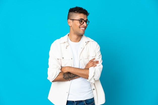 Jonge braziliaanse man geïsoleerd op blauwe muur op zoek naar kant