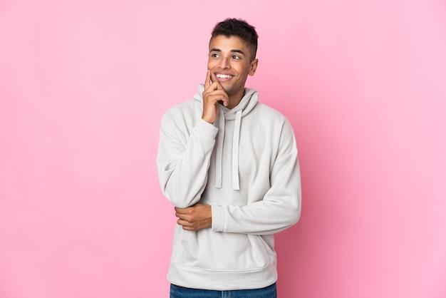 Jonge braziliaanse man geïsoleerd op roze muur een idee denken terwijl opzoeken