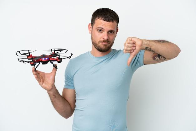 Jonge braziliaanse man met een drone geïsoleerd op een witte achtergrond met duim omlaag met negatieve uitdrukking