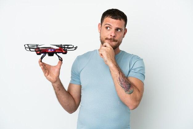 Jonge braziliaanse man met een drone geïsoleerd op een witte achtergrond met twijfels en denken