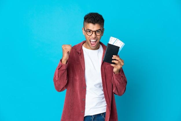 Jonge braziliaanse man over geïsoleerde muur gelukkig in vakantie met paspoort en vliegtickets