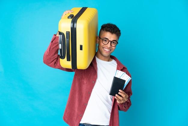 Jonge braziliaanse man over geïsoleerde muur in vakantie met koffer en paspoort
