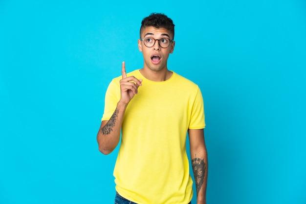 Jonge braziliaanse mens die op blauwe achtergrond een idee denkt die de vinger omhoog wijst