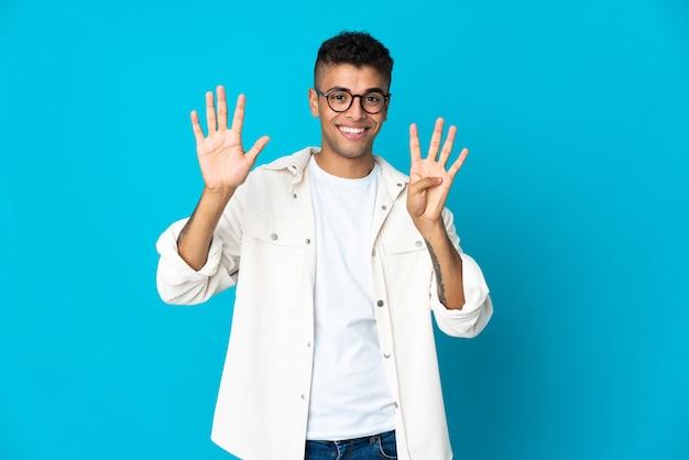 Jonge braziliaanse mens die op blauwe muur wordt geïsoleerd die negen met vingers telt