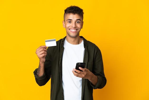 Jonge braziliaanse mens over geïsoleerd kopen met mobiel met een creditcard