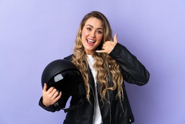 Jonge braziliaanse vrouw die een motorfietshelm houdt die op purple wordt geïsoleerd die telefoongebaar maakt. bel me terug teken