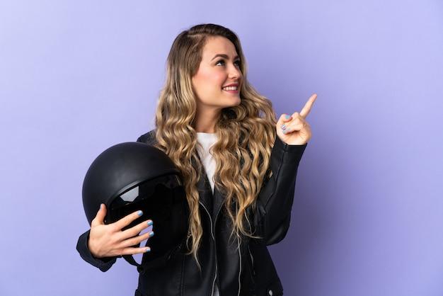 Jonge braziliaanse vrouw die een motorhelm houdt die op purpere achtergrond wordt geïsoleerd die een geweldig idee benadrukt