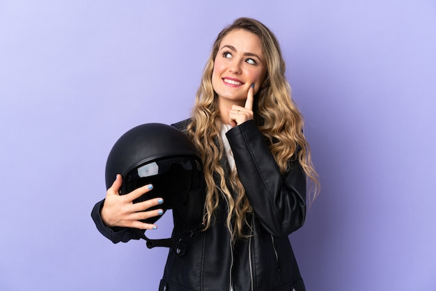 Jonge braziliaanse vrouw die een motorhelm houdt die op purpere achtergrond wordt geïsoleerd die een idee denkt terwijl het opzoeken